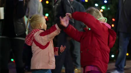 Slow motion - Two young children sisters dance together in front of a Christmas tree at night at a Christmas festival