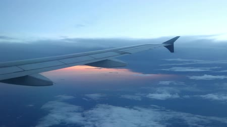 letadlo : Looking out a jet window at a blue cloudscape with the sunset reflecting off water in the distance