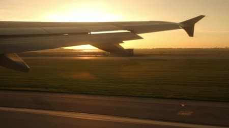 Looking out the window at the wing of a jet as it takes off the runway, with a brilliant sunset in the distance