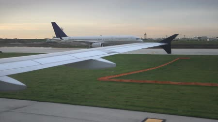 Looking out the window at the wing of a plane while moving down the runway, as another plane passes in the opposite direction logos have been obscured Dostupné videozáznamy