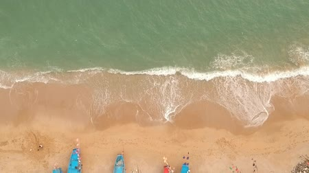 halászok : Aerial footage zooming from top to ground. A fisherman boats on the beach and wave from sea to beach... Stock mozgókép