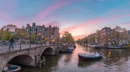 Нидерланды : Amsterdam city skyline day to night timelapse at canal waterfront, Amsterdam, Netherlands 4K Time Lapse