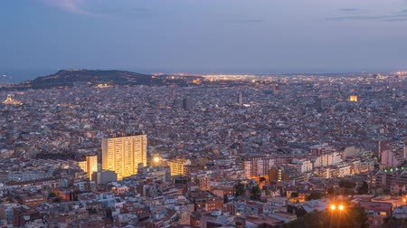 határkő : Barcelona Spain time lapse 4K, aerial view city skyline day to night timelapse from Bunkers del Carmel Stock mozgókép