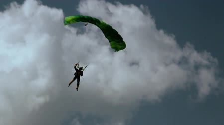 pára quedas : A person with a green parachute is slowly gliding and is about to land in the open field with hisher friends to cheer on them .  Vídeos