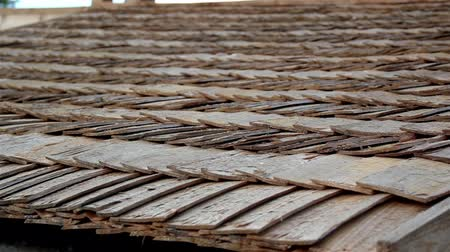 átfedés : A closer image of the pile of wooden shake roof of a house; very neat and clean. An up close view of the cedar shingle roof of the cabin log house wood that has been built for quilt some time enough to build up moss.  Stock mozgókép