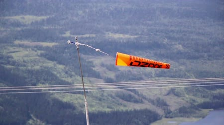 bavaria flag : Orange banner flag tied to a pole while swaying mid-air measuring wind speed in mountains. A banner were it looks like a kite and has a whole at its tail.
