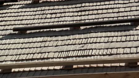 átfedés : Newly Placed roof tiles on the roof and some wood are placed at top to make sure its tightly in check. Cedar wooden shingle on the roof carpentry roofing roofworking build economy industry.