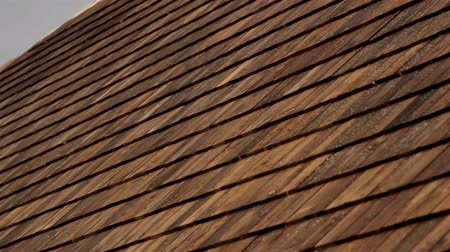 dekarz : A closer image of the wooden roof tiles that are found at the side of the house and check how big the house is. Cedar wooden shingle on the roof carpentry roofing roofworking build economy industry.