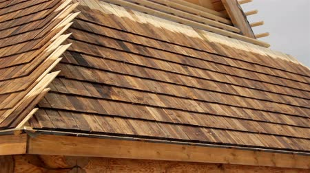 átfedés : Roof that has not been finished. An image of a roof that hasnt been fixed by the roofers completely. Cedar wooden shingle on the roof carpentry roofing roofworking build economy industry. Stock mozgókép