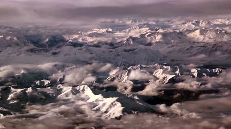 icefall : Clouds above rocky mountains that are covered with snow. This is a breathtaking view of the moutains.