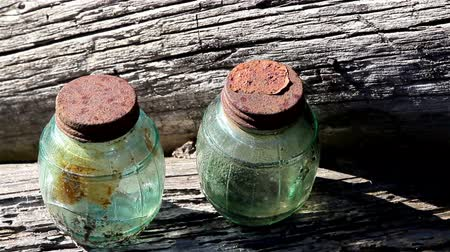 post and beam construction : Wooden blocks of the cabin house wall with 2 jars on them jars cover are rusty