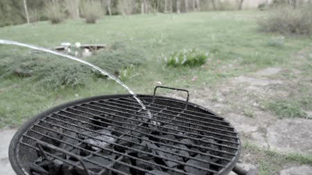 briquette : Putting water on the black coals on a grill in a garden