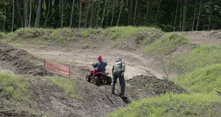 quadbike : An ATV car going uphill with a man pushing it