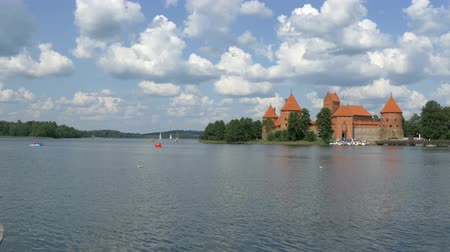 litvánia : A red in paint color medieval castle in Trakai Lithuania surrounded with a beautiful lake and some people are doing water bicycle 4K UHD Stock mozgókép