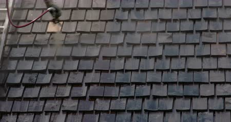 çatılar : Cleaning of the newly installed wooden shingles from the houses roof. The roofsmen uses a hose and ladder to go to the roof and clean the black shingles 4K