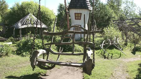 úgy néz ki : A wooden swing on the houses backyard. It looks like a big roots from a tree formed into swing Stock mozgókép