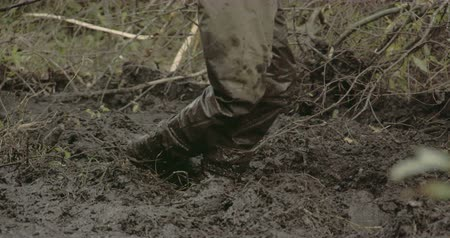 bahno : A man in boots walking onto the thick mud. He seems to be pulling a 4x4 offroad vehicle from being stucked