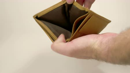 cüzdan : An empty brown wallet with two card inserted on the card divider. The man with a hairy hand opens the wallet and found no money Stok Video