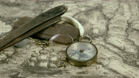 navigational : Few navigators things and a compass on the map. The eyeglass wooden razor and a ring