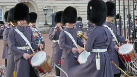buckingham palace : Palace band starting the beat with their drums. Coming from inside the band starts to play music and starts marching in 4K UHD