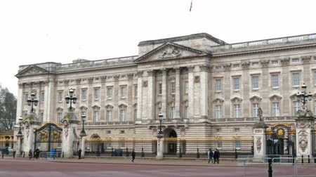 buckingham palace : Viewing of the Buckingham Palace across the street. People and cars are passing by the street infront of the gate in 4K UHD