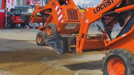 yönlendirmek : Demonstration demonstration of the possibilities of mini-loaders. Construction machinery at work. Stok Video