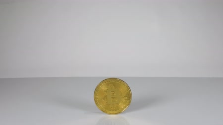 кошелек : A single Bitcoin coin rolling past the field of view. Стоковые видеозаписи