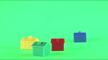 espaço de texto : A collection of plastic houses moving horizontally to give the concept of relocation. Taken against a solid green screen color. Stock Footage