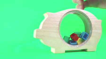 piggy bank : A wooden piggy bank being filled one by one with plastic houses to give the concept of saving for a new home. Taken against a solid green screen color. Stock Footage