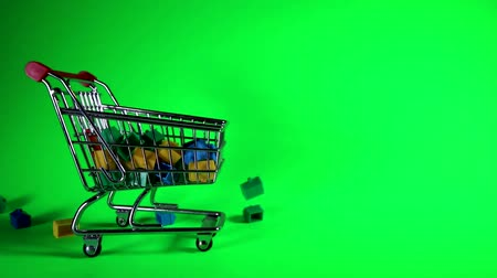 vrijstaand huis : A load of plastic houses falling from above into a trolley to give the concept of price fall. Taken against a solid green screen color.