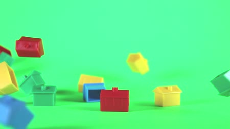 vrijstaand huis : A collection of plastic houses moving horizontally to give the concept of relocation. Taken against a solid green screen color. Stockvideo