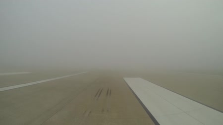 tarmac : A view of a runway at one of the UKs largest growing airports. Here fog obscures and delays arrivals and departures. Stock Footage