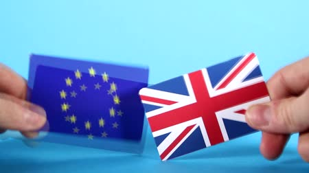 decidir : The European Union and Union Jack flags being handled against a bright blue background.