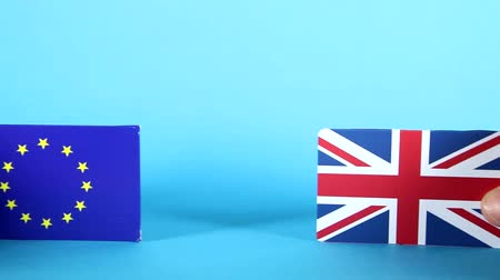 dönt : The European Union and Union Jack flags being handled against a bright blue background.