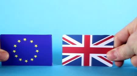 оставлять : The European Union and Union Jack flags being handled against a bright blue background.