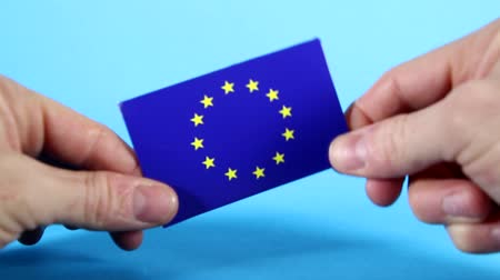 união : The European Union flag being handled against a bright blue background.