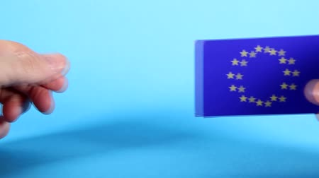 Észtország : The European Union flag being handled against a bright blue background.