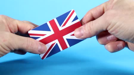 оставлять : The Union Jack, British, flag being handled against a bright blue background. Стоковые видеозаписи
