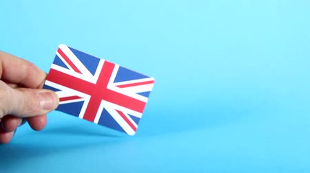 handling : The Union Jack, British, flag being handled against a bright blue background. Stock Footage