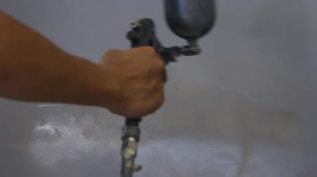 repaint : Close-up. Worker spraying grey paint on the fuel tank. Stock Footage