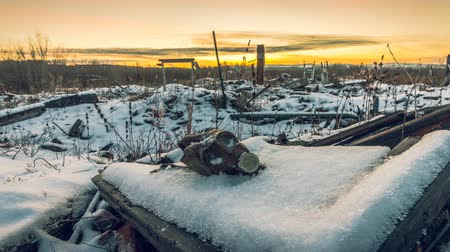 judgment day : The post-apocalyptic world.Nuclear winter.Old gas mask in the ruins. The remains of houses covered with snow at sunset