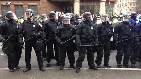 authoritarian state : WASHINGTON, Jan. 20, 2017 -- Police in riot gear with batons and helmets form a line surrounding detained DisruptJ20 protesters during the presidential inauguration of Donald Trump.
