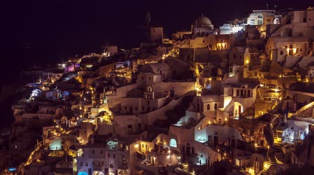УВР : View of Oia village, island of Santorini, Greece, at night with people rushing around, timelapse, tilt, pan, zoom