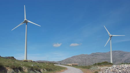 blade : Two wind turbines and road in-between in hill landscape on clear sunny day Stock Footage