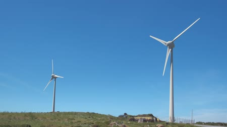 회 전자 : Diagonal shot of two wind turbines and road in-between in hill landscape on clear sunny day