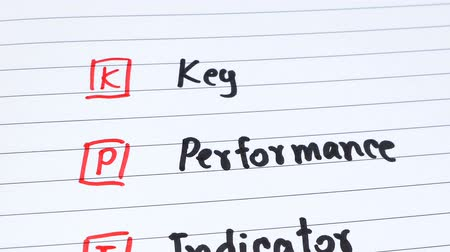 metrik : Motion video of handwriting KPI (Key Performance Indicator) on white notebook with wood background (Business concept) Stok Video