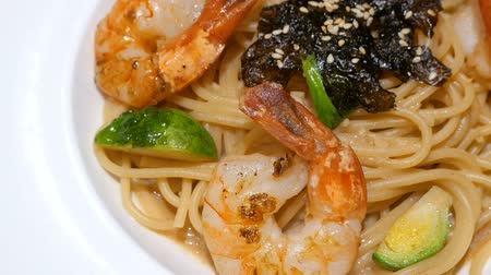 dish : Motion video of seafood pasta  Spaghetti with shrimp on white dish (Selective Focus)