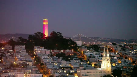 história : View of Coit Tower and St. Peter and Paul church at night, from Lombard street. Coit tower is lit red and gold in honor of the SF 49ers making the NFL playoffs.