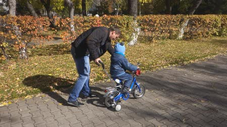 país : Steadicam shot of father teaching son how to ride his bike on a park pathway with safety helmet. Vídeos