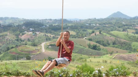 sundurma : Man holding the rope The swing chair and play happily Background mountains at The wind farm in Khao Kho, Phetchabun in Thailand. July 14, 2019